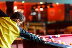 Cute boy in yellow t shirt plays billiard or pool in club. Young Kid learns to play snooker. Boy with billiard cue. Strikes the ball on table. Active Leisure royalty free stock photo