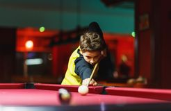 Cute boy in yellow t shirt plays billiard or pool in club. Young Kid learns to play snooker. Boy with billiard cue. Strikes the ball on table. Active Leisure stock photo