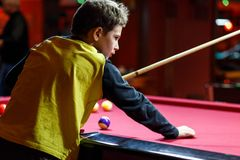 Cute boy in yellow t shirt plays billiard or pool in club. Young Kid learns to play snooker. Boy with billiard cue. Strikes the ball on table. Active Leisure stock images