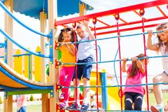 Educational quests for children. Cute boys and girls climb on the rope net on the playground stock photos