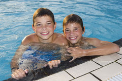 Cute boys swimming and playing in water. Activities on the pool. Cute boys swimming and playing in water in swimming pool Stock Photos