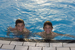 Cute boys swimming and playing in water. Activities on the pool. Cute boys swimming and playing in water in swimming pool Royalty Free Stock Photography