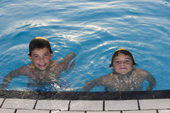 Cute boys swimming and playing in water. Activities on the pool. Cute boys swimming and playing in water in swimming pool Royalty Free Stock Photo