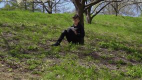 Cute boys writes poem sitting under flower tree on grass in park. Teenager in leather jacket sits under blooming tree in park and writes a poem in his workbook stock video
