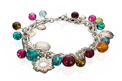 Cute bracelet made of glass and metal beads. Cute bracelet made of colorful glass beads and metal charms attached to a silver chain on a white background Stock Photo