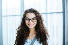 Cute brazilian girl with curly hair and casual clothing smiles for the camera stock image