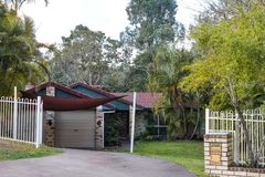 Cute brick Australian house with tile roof and awning snuggled back into the tropical rainforest. A Cute brick Australian house with tile roof and awning Stock Photos