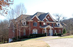 Cute Brick Luxury Home 27. Brick multi-story home with white trim and angled roof Stock Image