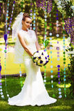 Cute bride in beautiful flower arch Stock Image