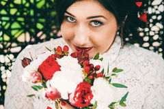 Cute bride with bouquet of red flowers Royalty Free Stock Photo