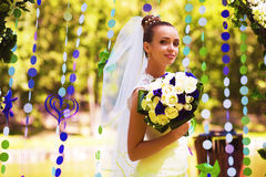 Cute bride in flower arch with bouquet Stock Image