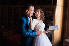 Cute bride and groom embracing witn book near window  at old library Royalty Free Stock Photography
