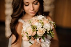 Cute bride holding wedding bouquet of white and peach roses. Cute stylish bride holding a gentle wedding bouquet of white and peach roses with silk ribbon stock photography