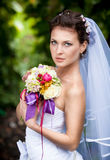 Cute bride with long veil holding bouquet Stock Photo