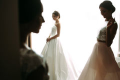 Cute bride next to the window with her friends Royalty Free Stock Photo