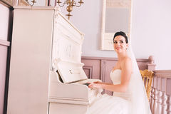 Cute bride playing the piano Royalty Free Stock Image