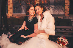 Cute bride with sister on bench Royalty Free Stock Images