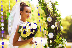 Cute bride under flower arch with bouquet Royalty Free Stock Photography