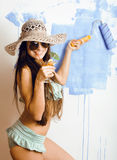 Cute bright woman in sunglasses and hat with cocktail in bikini in studio Stock Photo