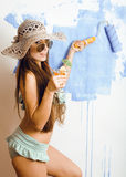 Cute bright woman in sunglasses and hat with cocktail in bikini in studio Stock Photos