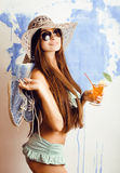 Cute bright woman in sunglasses and hat with cocktail in bikini in studio Stock Image