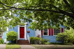 Cute brightly painted blue shingled cottage with red and white trim under a big tree stock photos