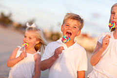 Cute Brother And Sisters Enjoying Their Lollipops Outside Stock Photos