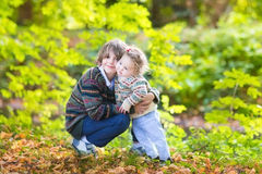Cute brother and his baby sister hugging in park Royalty Free Stock Image