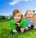 Cute brother and little sister in park. Cute brother and his little sister laying on green grass in park Royalty Free Stock Image