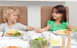 Cute brother and sister holding their hands. Before lunch in the kitchen Royalty Free Stock Photos