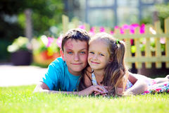 Cute brother and sister lying on the grass Stock Image