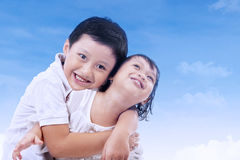 Cute brother and sister under blue sky Royalty Free Stock Photography