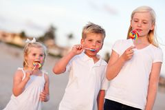 Cute Brother and Sisters Enjoying Their Lollipops Royalty Free Stock Photo