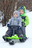 Cute brothers on sleigh. In snow park Royalty Free Stock Photos