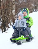 Cute brothers on sleigh. In snow park Royalty Free Stock Image