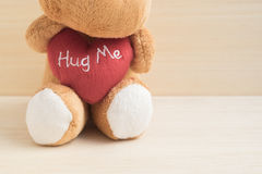 Cute brown doll hug red heart Stock Image