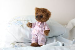 Cute brown teddy bear in pajamas in the bed Royalty Free Stock Images