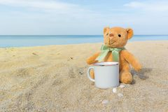 Cute brown teddy bear sitting on the beach with a coffee cup. Concept for relaxation, comfort and holiday with copy space stock photography