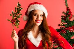 Cute brunete girl in santa claus dress with presents for christm Royalty Free Stock Photos