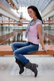 Cute brunette on  bench over mall background. Portrait of a cute brunette on a bench over mall background Stock Photos