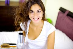 Cute brunette blow drying long hair at home in bed smiling happy Stock Image