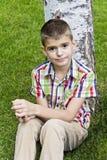 Cute brunette boy eleven years old. Sitting near tree royalty free stock photo