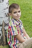 Cute brunette boy eleven years old. Sitting near tree royalty free stock photos