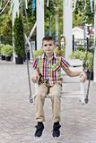 Cute brunette boy ride on a swing. In summer stock images