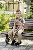 Cute brunette boy are sitting on the bench. In summer stock image