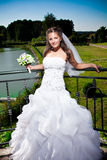 Cute brunette bride standing against lake at park Stock Photo