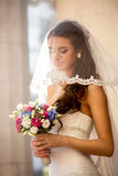 Cute brunette bride with wedding bouquet at sunny day Royalty Free Stock Image