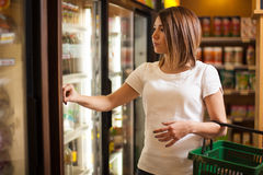 Cute brunette buying some groceries. Pretty young woman carrying a basket and looking at some products in a refrigerator at the supermarket Stock Photos