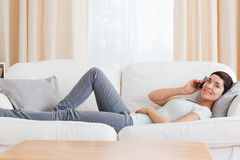 Cute brunette calling while lying on a sofa Stock Images