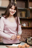 Cute brunette cooking in a home kitchen.Young beautiful smiling woman breaks an egg into the flour to the dough. Young beautiful smiling woman breaks an egg into royalty free stock photography